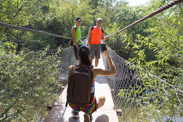 Young Travelers, hikers with backpack take photos on the a suspension bridge. Travel concept